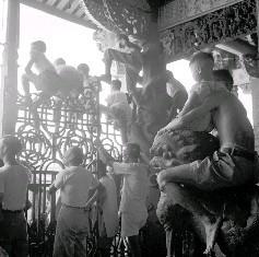男信徒不僅抱著小孩坐在石獅上,更誇張的是小孩居高臨下的險境,還真令人膽顫心驚