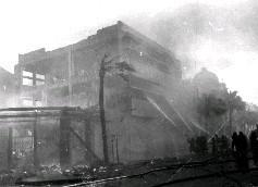 煙霧朦朧的照片中,依稀可見警消人員集中資源,以四道強力水柱灌救火場